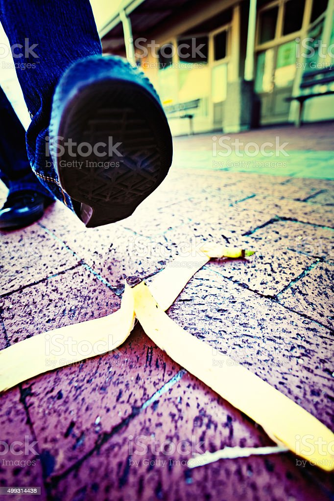 Anonymous foot approaching dropped banana peel, possible accident coming up stock photo