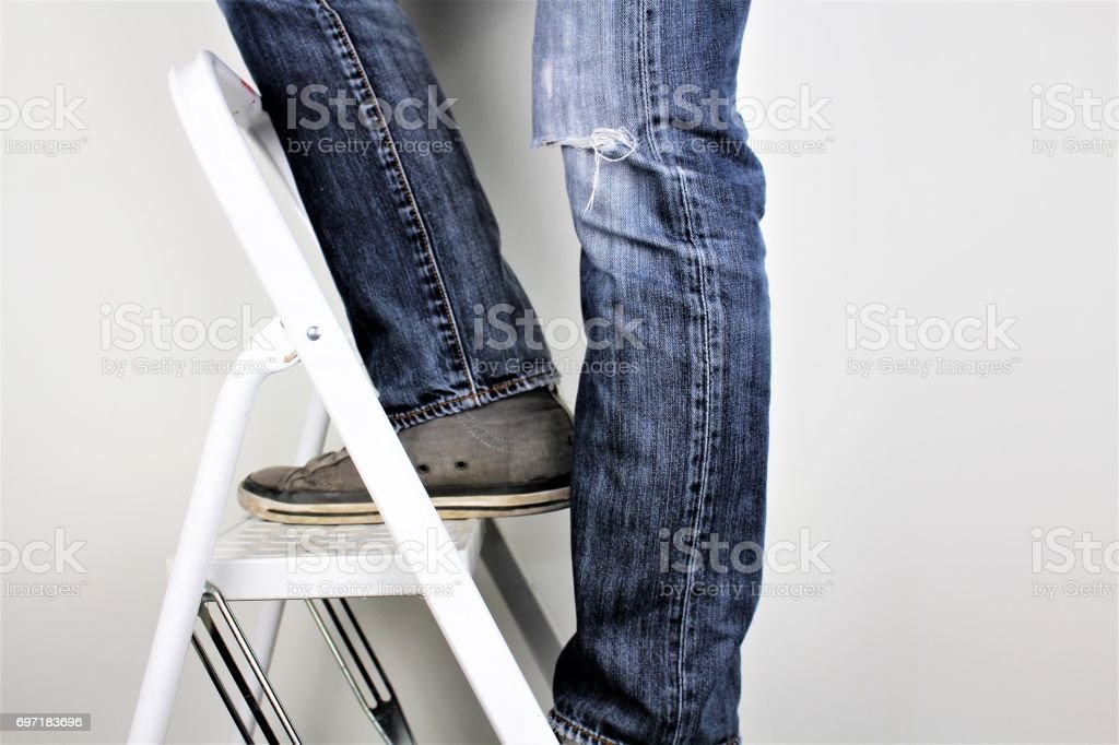 Anonymous man reaching on top of ladder climbing, indoors studio people shot stock photo