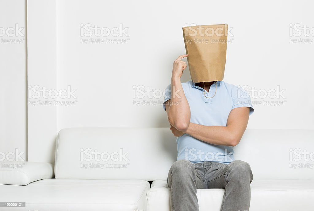 Anonymous man sitting on sofa and thinking. stock photo