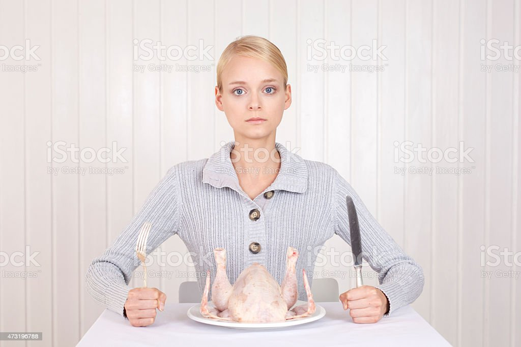 Anorectic woman in front of plate with raw roast goose stock photo