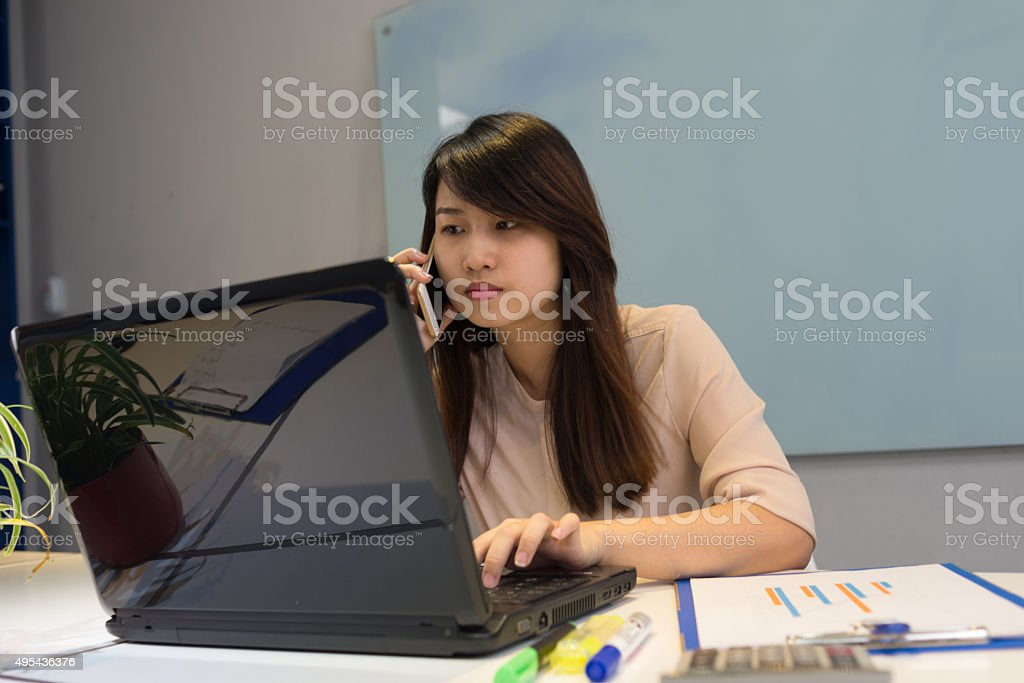 Answering call while using laptop in meeting room stock photo
