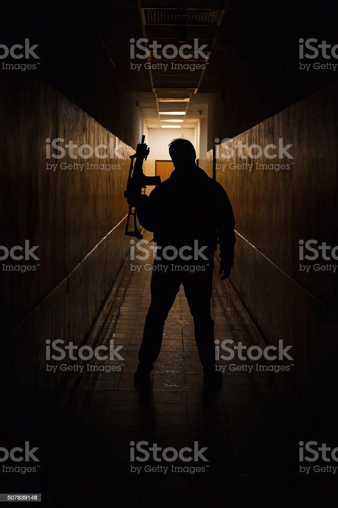 Anti terrorist dressed in camouflage, standing with gun, studio shot stock photo