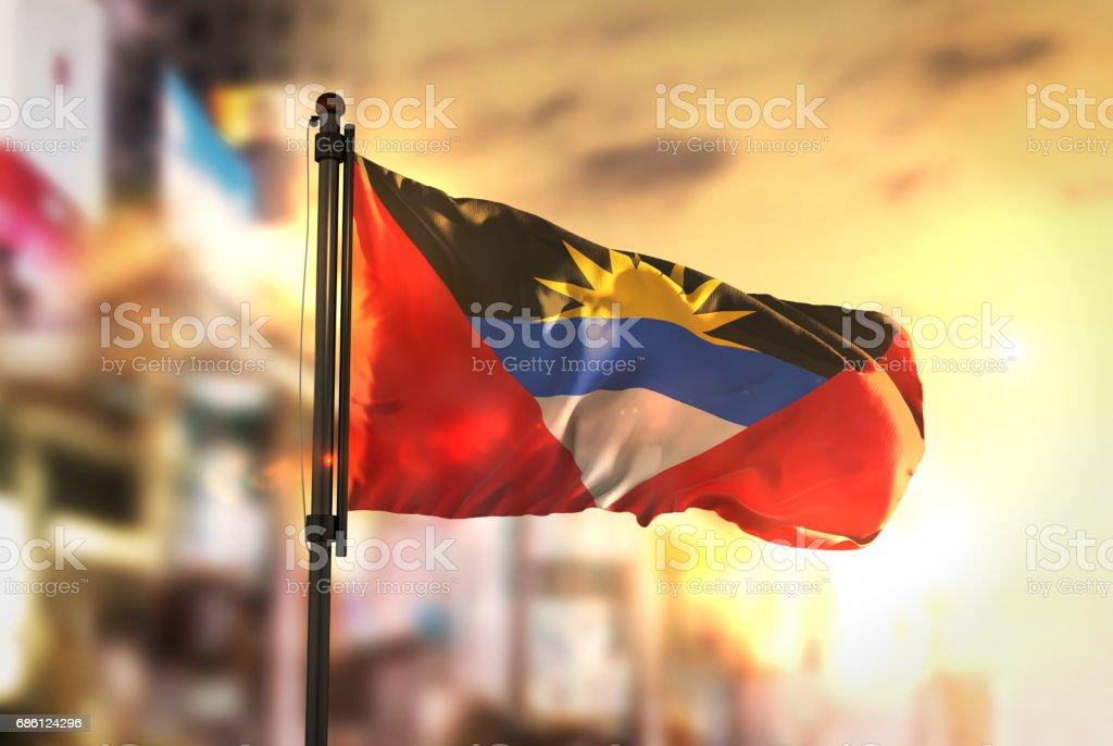 Antigua and Barbuda Flag Against City Blurred Background At Sunrise Backlight stock photo