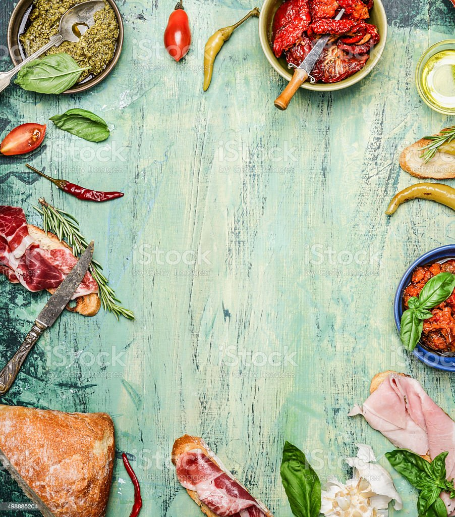 Antipasti with ciabatta bread, pesto and ham on rustic background stock photo