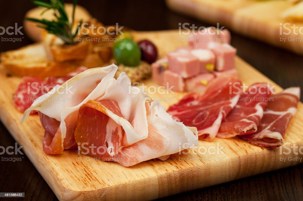 Antipasto board with prosciutto salami and other goodies stock photo