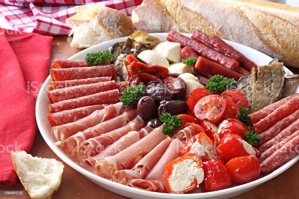 Antipasto plate with rolled meats, tomatoes, and olives stock photo
