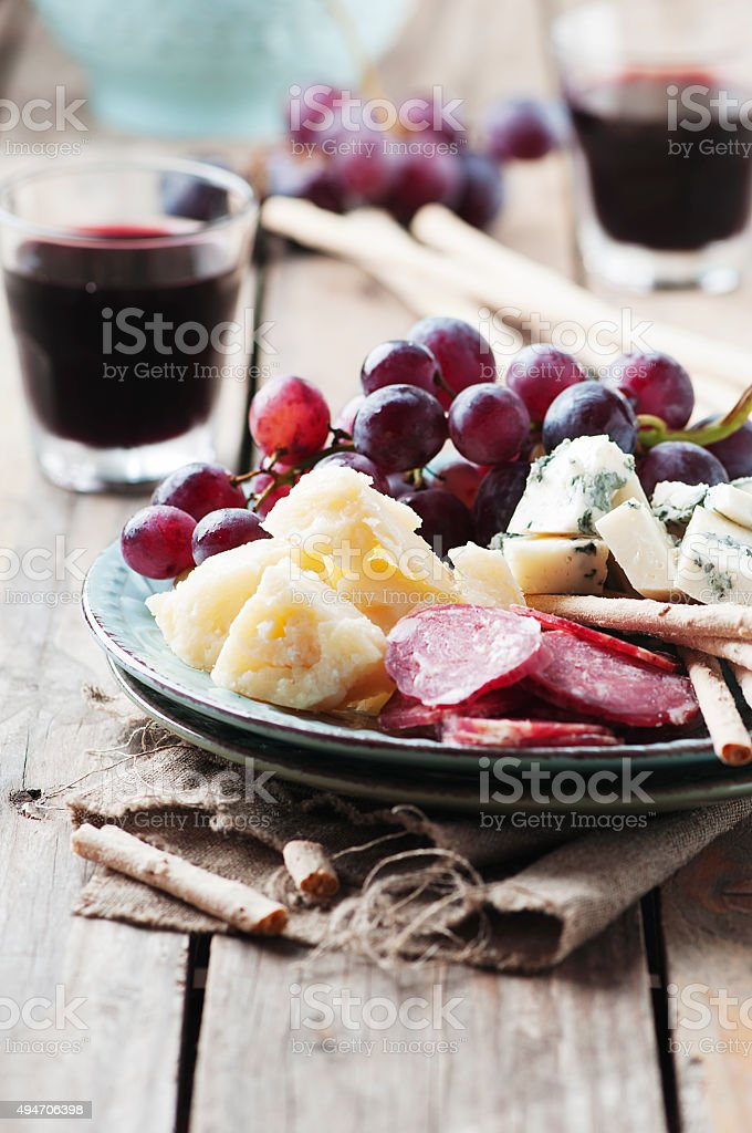 Antipasto with cheese, sausage and grape stock photo