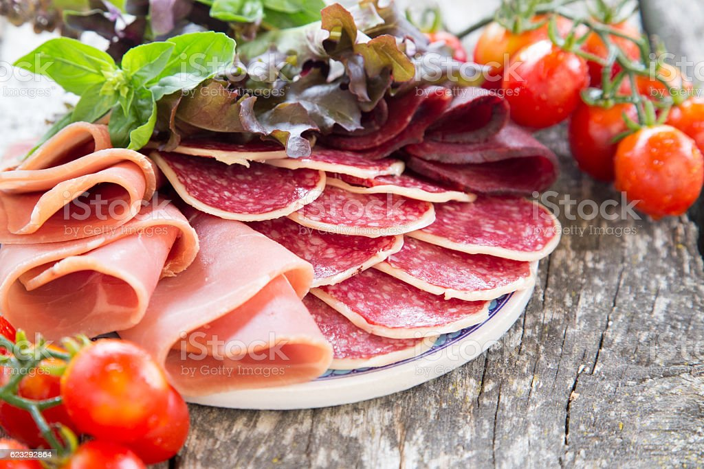 Antipasto with ham, salami and bresaola. tomato and basil. stock photo