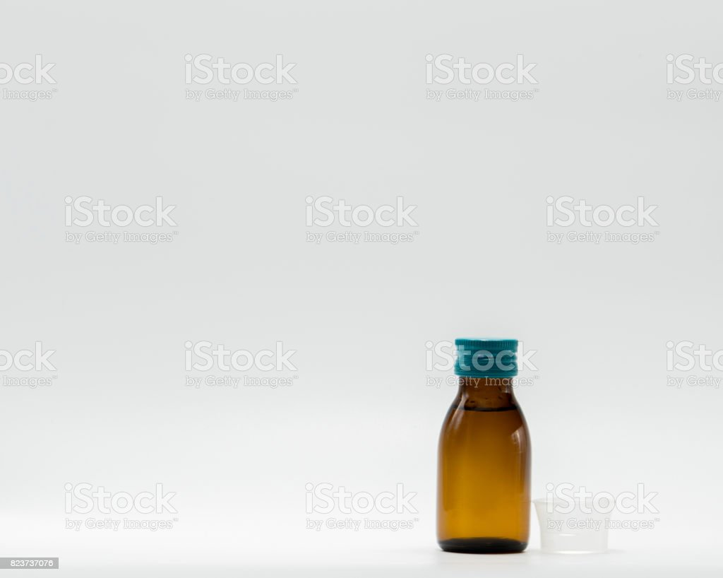 Antipyretic syrup in amber bottle with blank label and a plastic measuring cup on white background stock photo