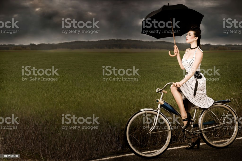 Antique Bike with Beautiful Brunette Young Woman in Stormy Weather stock photo