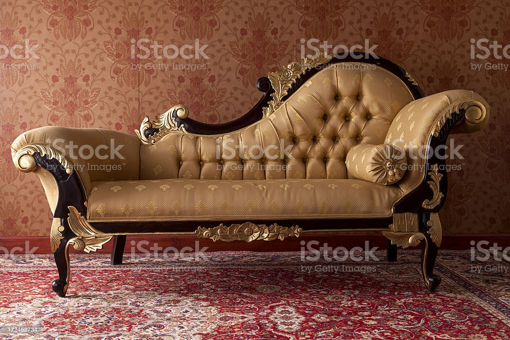 Antique black and gold chaise lounge in red room stock photo
