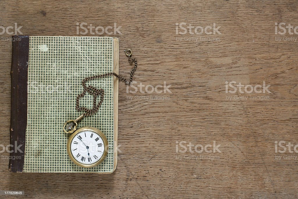 Antique book and old vintage pocket watch on wooden background royalty-free stock photo