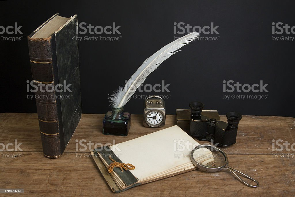 Antique book, magnifying glass, notepad, quill, inkwell, binoculars, clock royalty-free stock photo