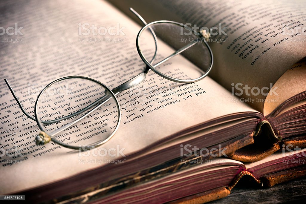 Antique books and spectacles stock photo