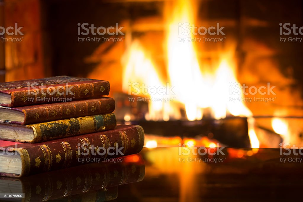 Antique books in front of warm fireplace. Magical cozy atmosphere stock photo