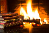 Antique books in front of warm fireplace. Magical cozy atmosphere