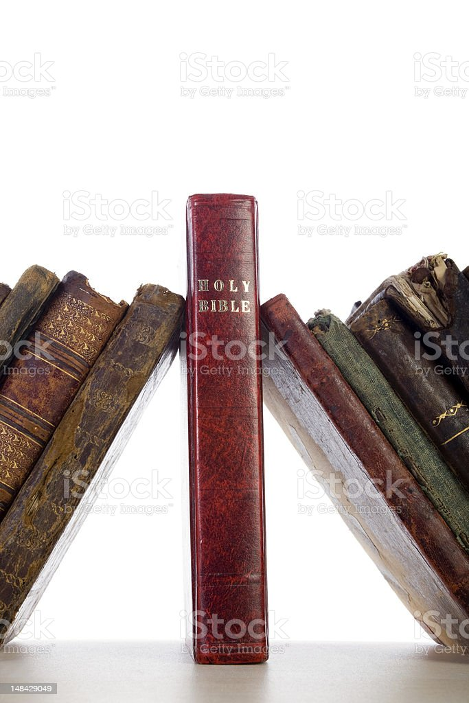 Antique Books Leaning On Holy Bible As Keystone stock photo