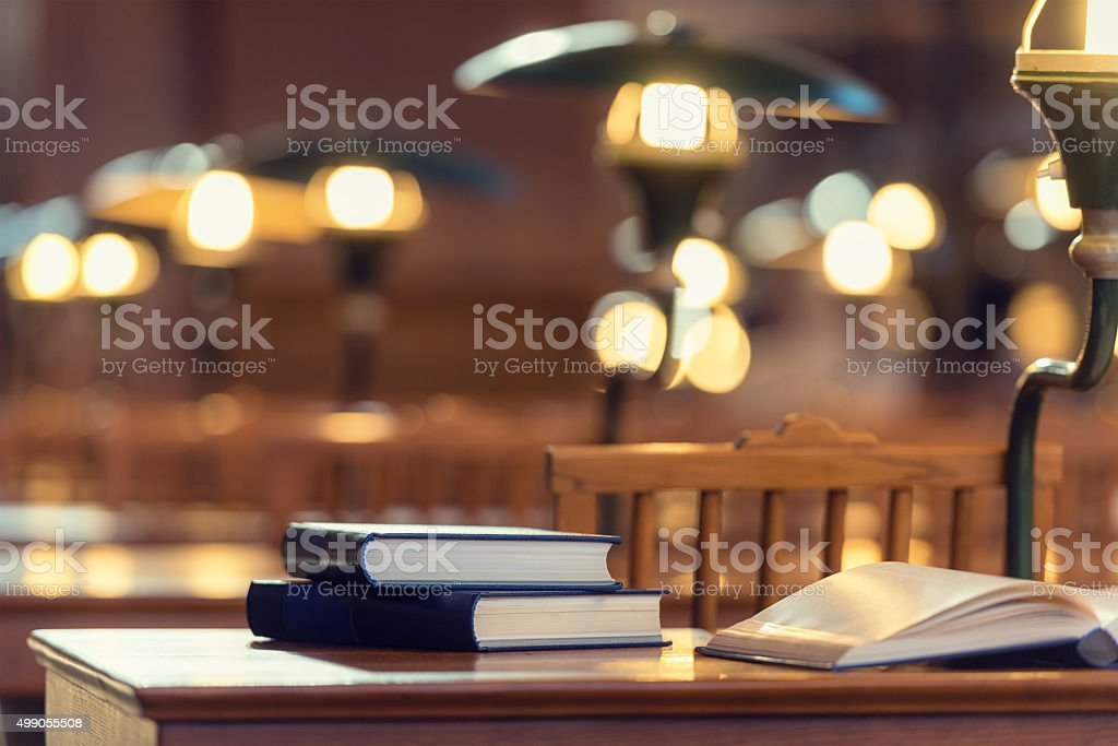 Antique books on a desk with a lamp stock photo