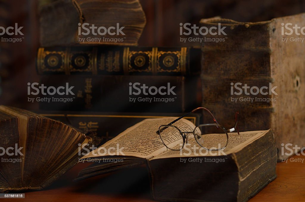 antique books with reading glasses in a dusty room stock photo