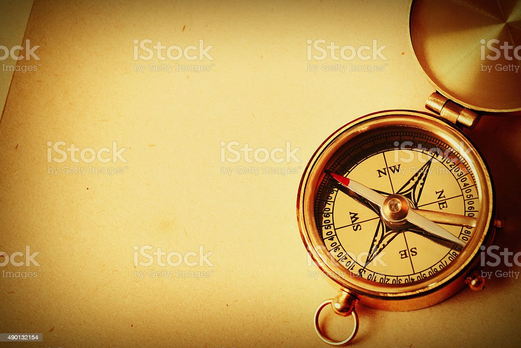 Antique brass compass over old background stock photo