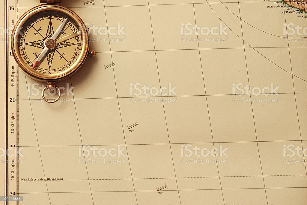 Antique brass compass over old map stock photo