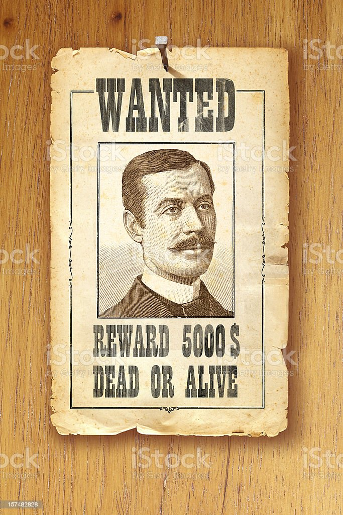 Antique brown wanted poster fixed with nail on wooden background royalty-free stock photo