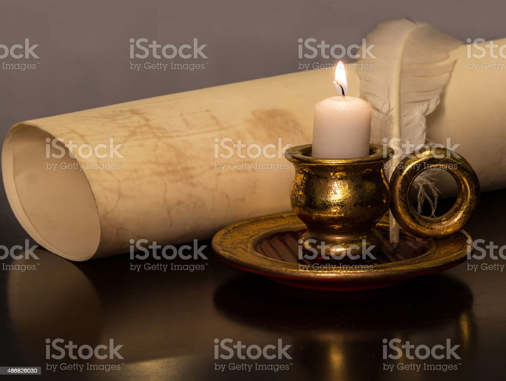 Antique Candle with a feather and parchment stock photo