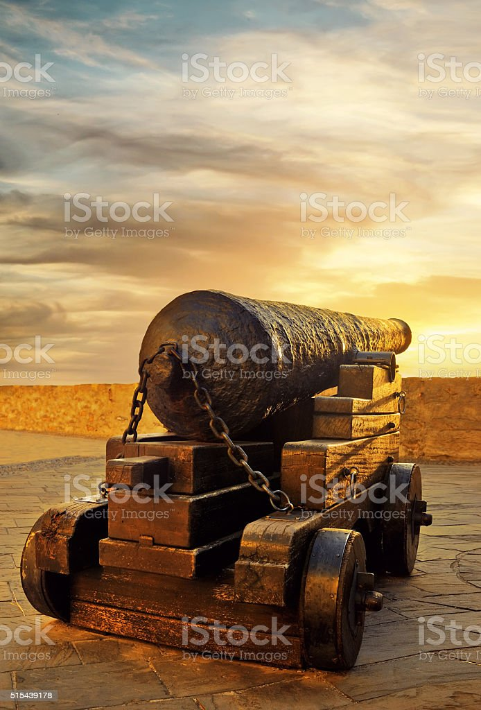 antique cannon on nuclei at sunset stock photo