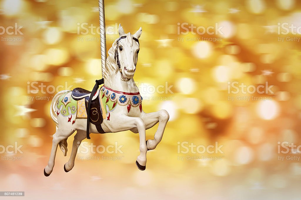 Antique carousel horse, golden festive lights background stock photo