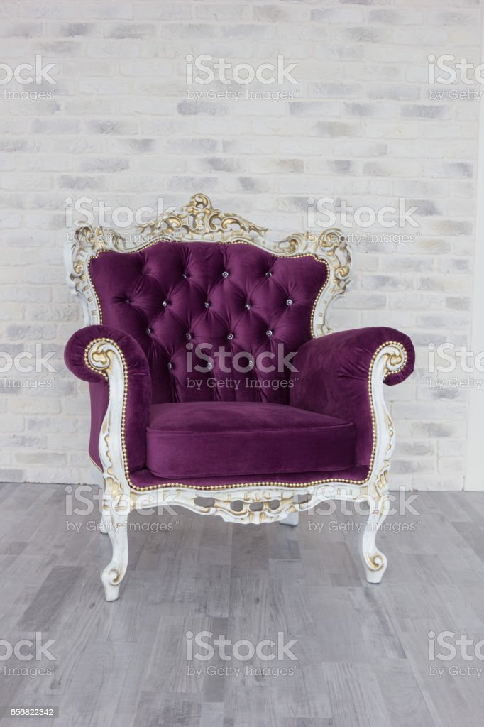 Antique chair from purple velvet in front of white room stock photo