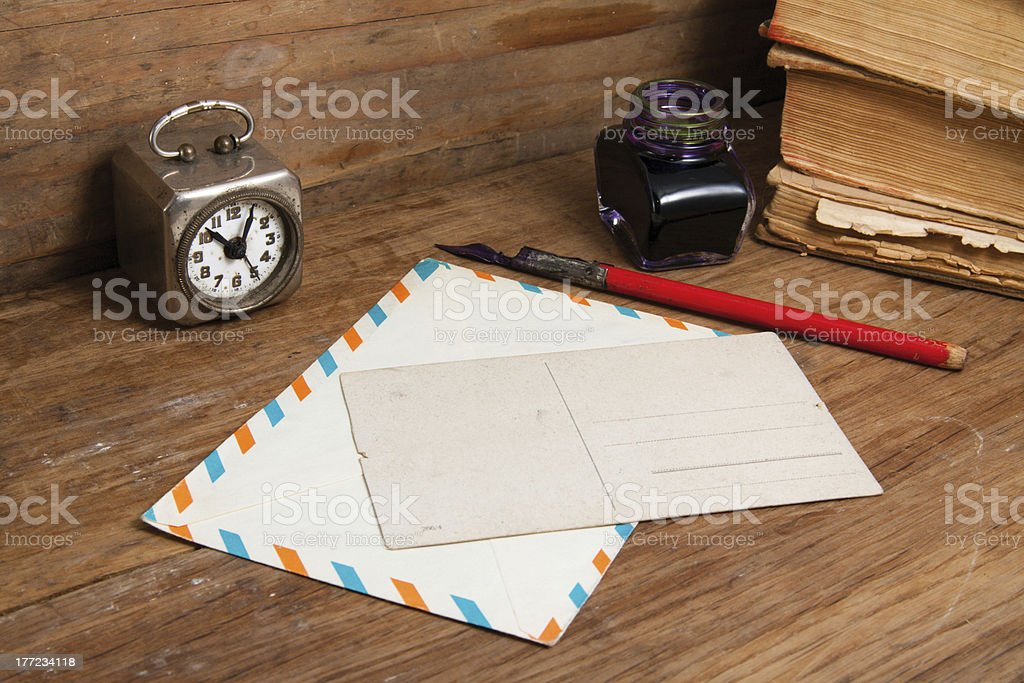 Antique clock, postcard, envelope, ink pen and inkwell on wood royalty-free stock photo