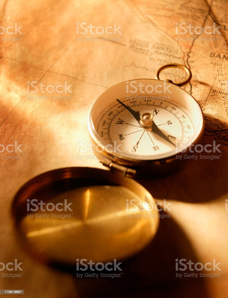 Antique Compass Sitting On Antique Map Warmly Lit royalty-free stock photo