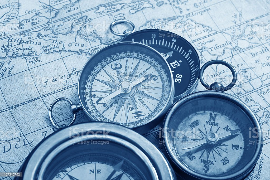 Antique compasses in an antique map in shades of blue stock photo