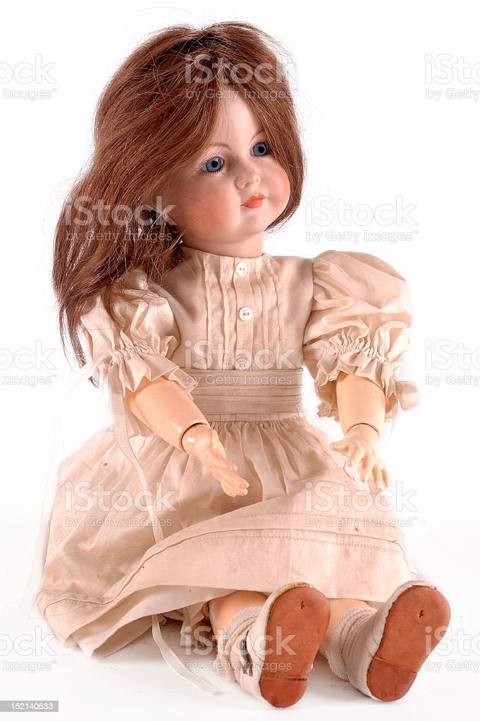 Antique doll sitting in a light pink dress stock photo