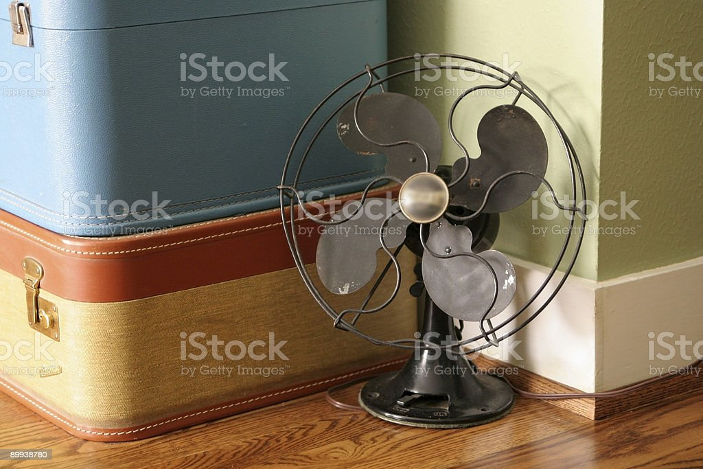 Antique fan with suitcases in background stock photo