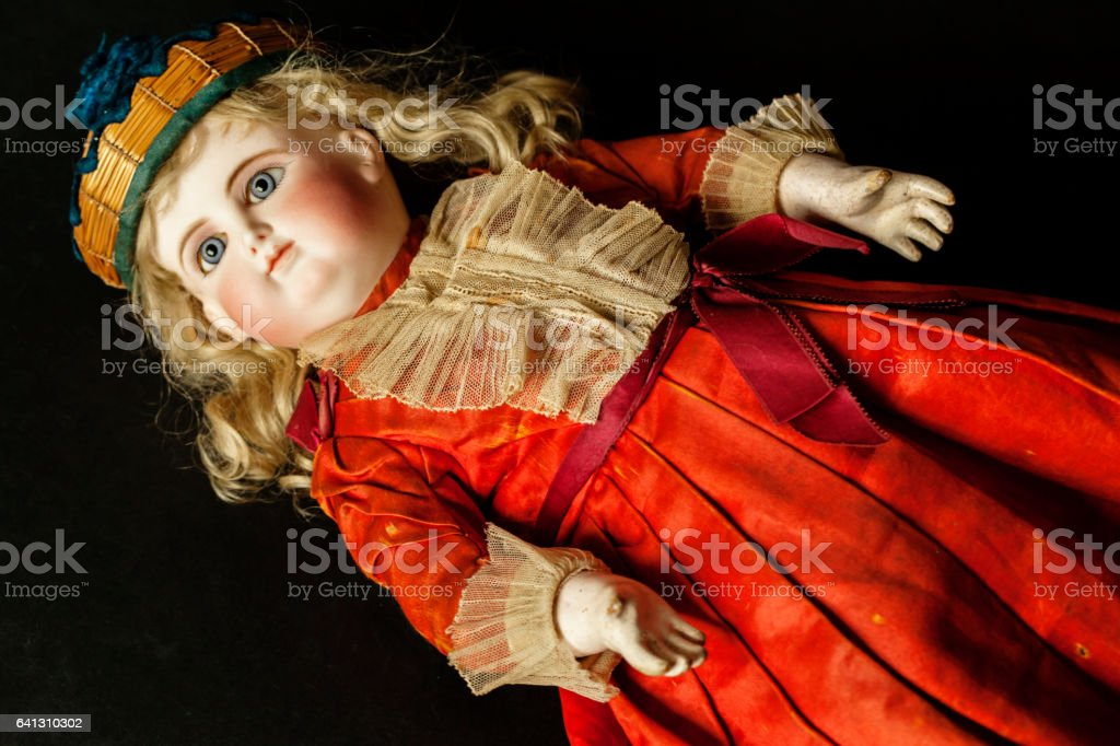 Front view of French 1880\'s doll, placed on a table, with blue spiral...