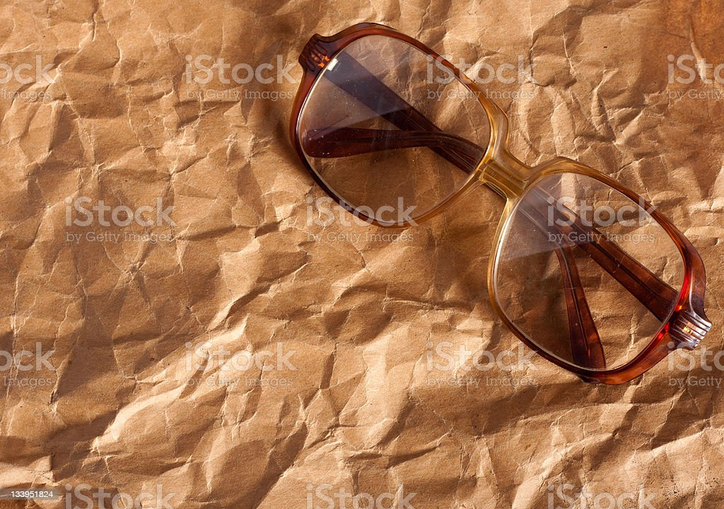 Antique glasses on old crumpled paper royalty-free stock photo