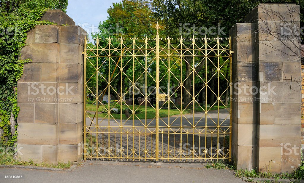 Antique golden gate leading cemetery park sandstone wall royalty-free stock photo