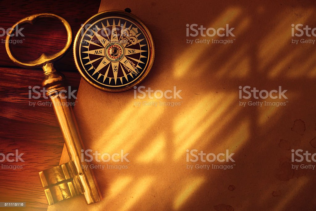 Antique golden key and compass with shadow stock photo