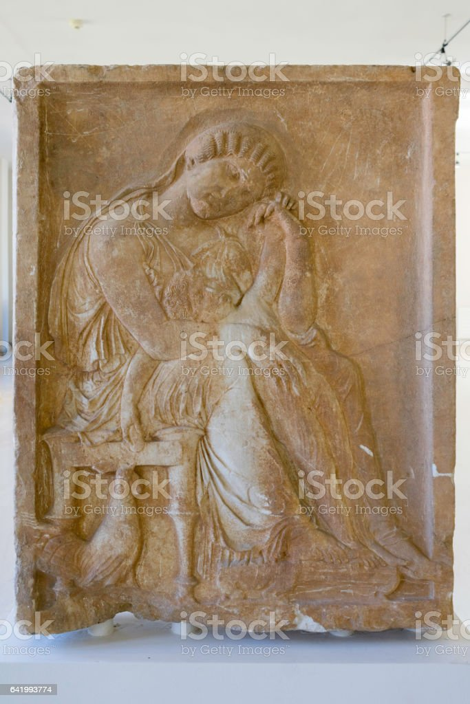 Antique Greek bas-relief with woman fragment on desk stock photo