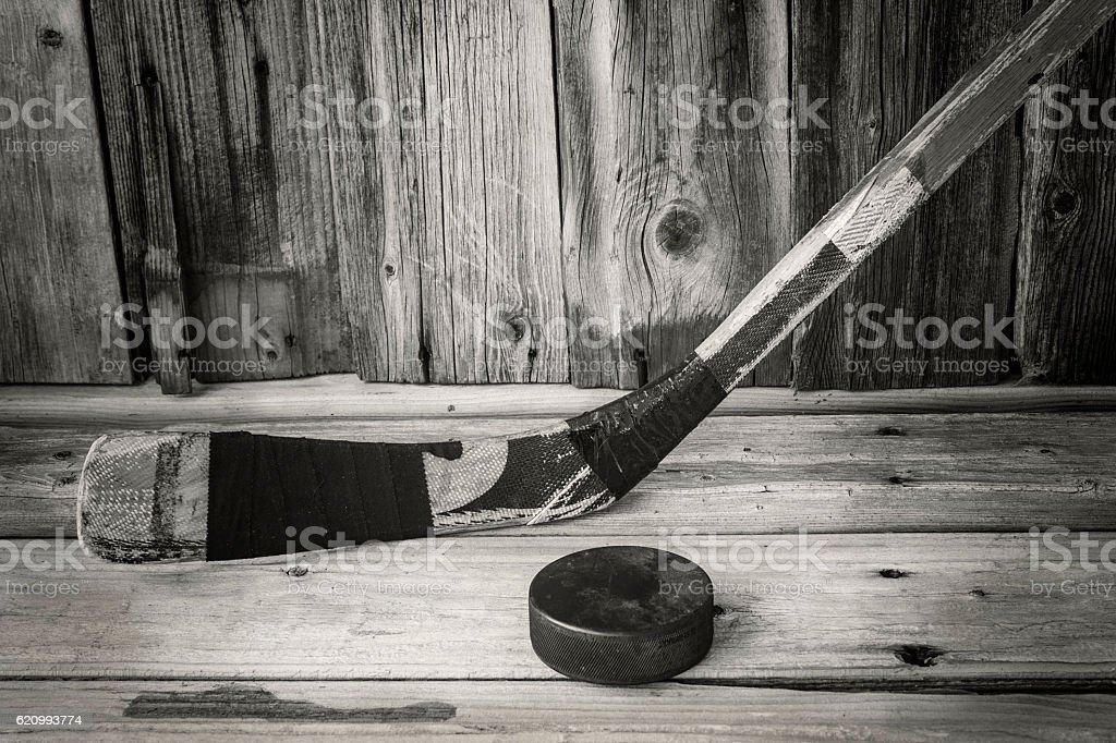 antique hockey stick with puck on old rustic wood background stock photo