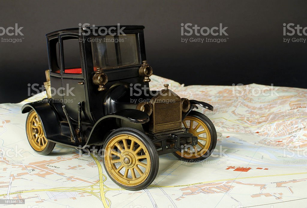 Antique iron toy car on the road map royalty-free stock photo