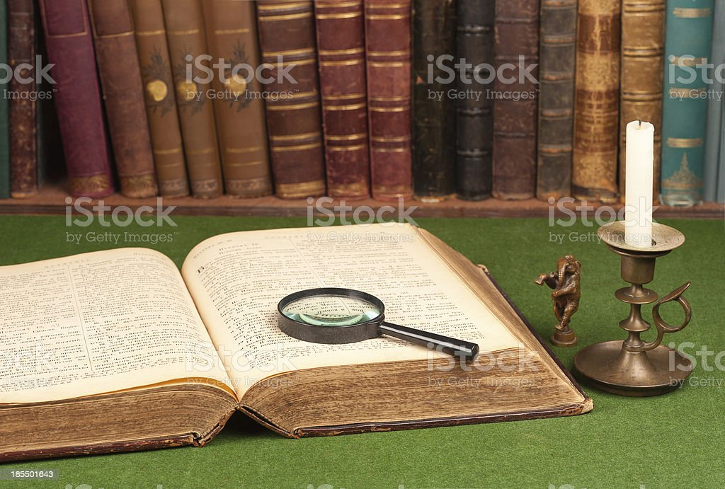 Antique leather books, tin candlestick and magnifying royalty-free stock photo