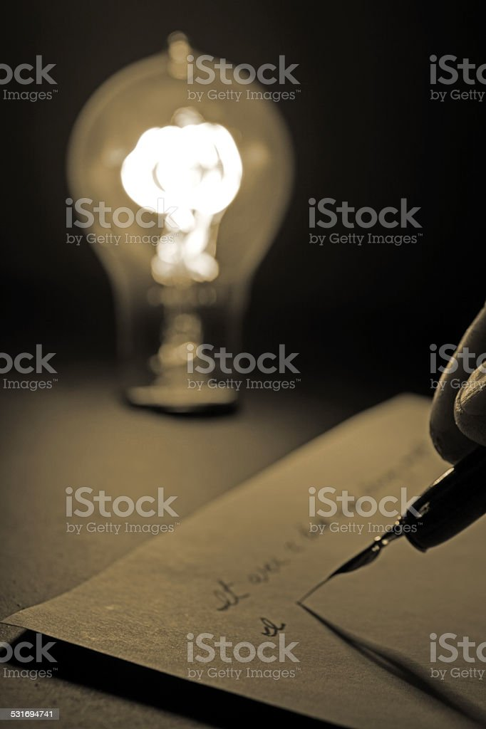 Antique Light Bulb and Hand Held Antique Pen stock photo