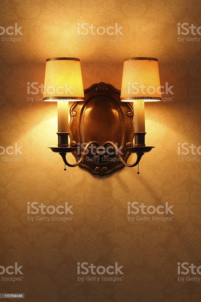 Antique Lighting Fixture Against Old Patterened Wallpaper royalty-free stock photo