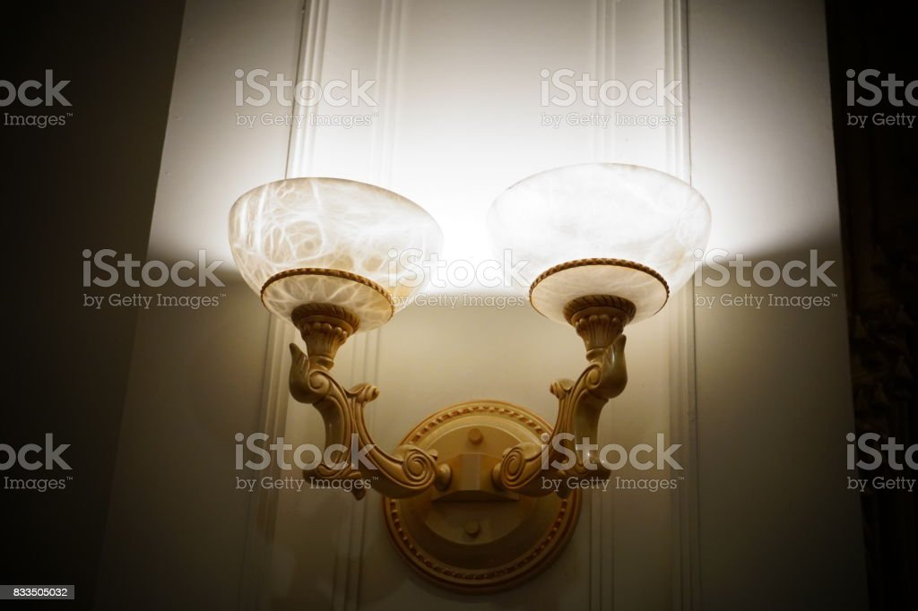 Antique Lighting Fixture Against Old Patterned Wallpaper stock photo