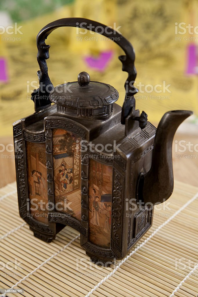 Antique metal Asian teapot on a bamboo mat royalty-free stock photo