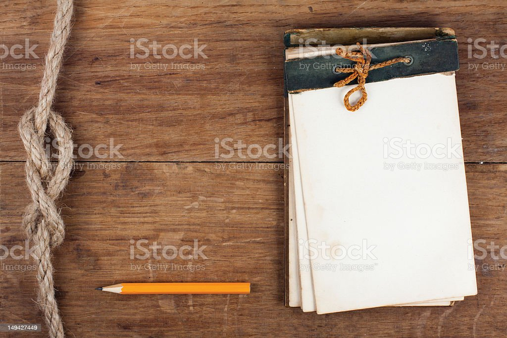Antique notebook and pencil, rope knot on wood background royalty-free stock photo