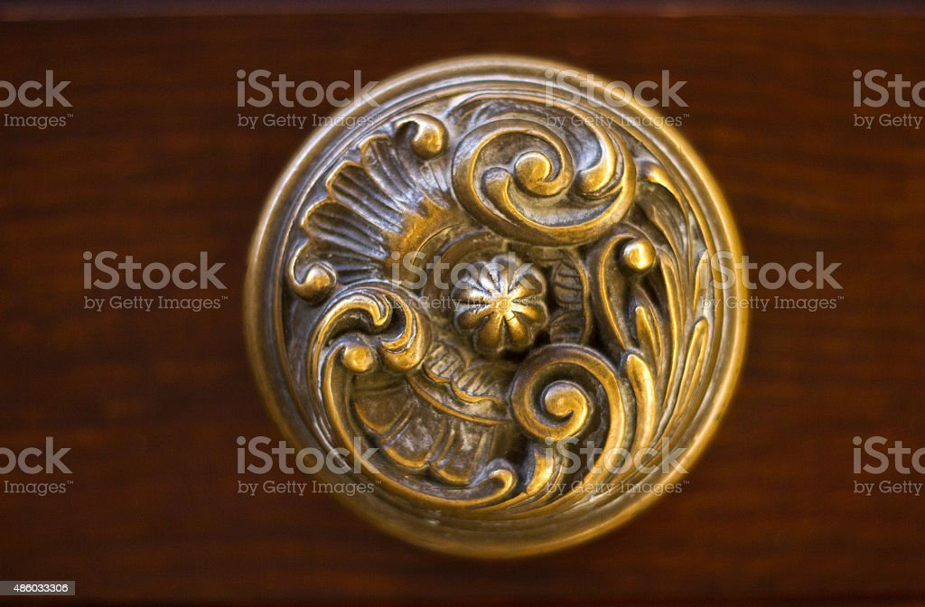 Antique Ornate Bronze Doorknob on Brown Door (Close-Up) stock photo