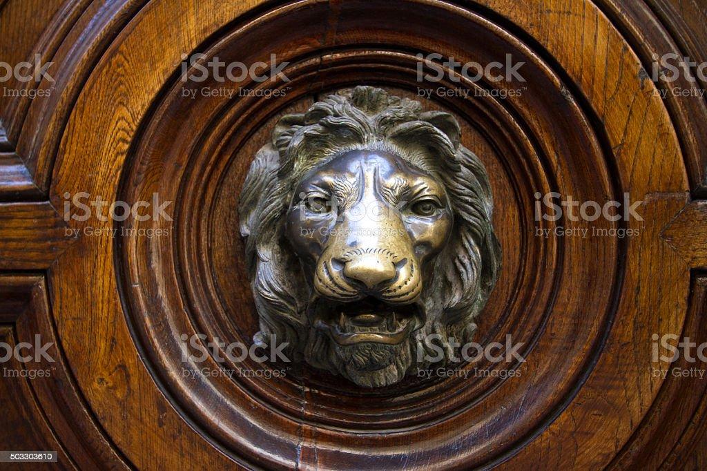 Antique Ornate Bronze Lion Doorknob on Brown Door (Close-Up) stock photo